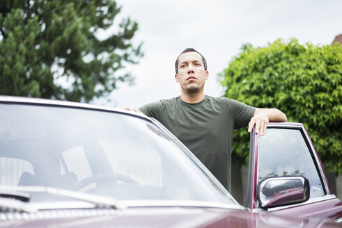 Serious man standing beside car - MOEF00149