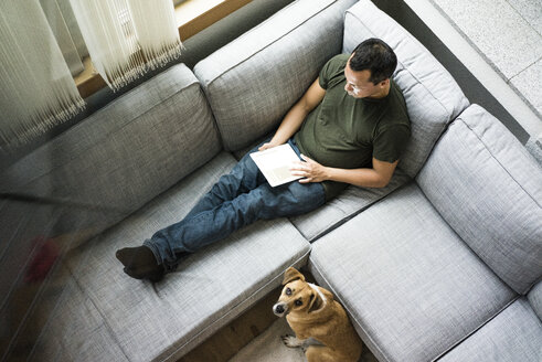 Man at home using tablet on the couch with dog beside him - MOEF00167