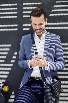 Portrait of businessman with longboard and phone near concrete wall - BSZF00009