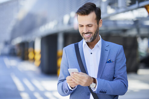 Portrait of businessman using phone on parking level in the city - BSZF00012