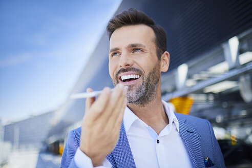 Portrait of cheerful businessman with phone in the city - BSZF00015