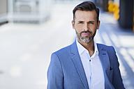 Confident businessman standing outdoors - BSZF00018