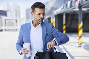 Businessman checking time and holding coffee outdoors - BSZF00021