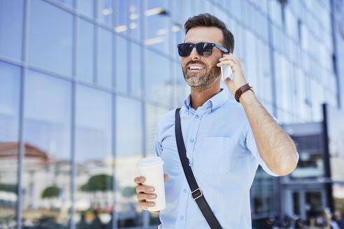Cheerful businessman talking on phone and holding coffee outdoors - BSZF00030