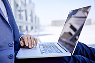 Close-up of businessman using laptop outdoors - BSZF00042