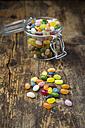 Glass of colourful sweet jellybeans on dark wood - LVF06299