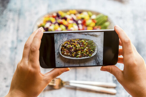 Girl taking picture of Quinoa salad with smartphone, close-up - SARF03375