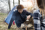 Couple camping in forest - ZOCF00507