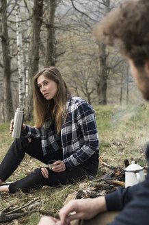 Woman with thermos flask at campfire in forest - ZOCF00510