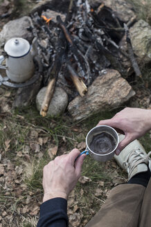 Man drinking coffee at campfire - ZOCF00513