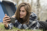 Smling woman lying on meadow next to tent looking at cell phone - ZOCF00516