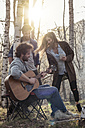 Friends in forest with man playing guitar - ZOCF00522