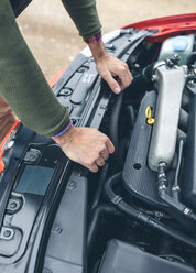 Close-up of man checking car engine - DAPF00818