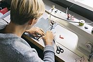 Woman using sewing machine on table in studio - JUBF00285