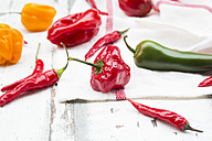Various chili pods on kitchen towel and wood - LVF06309