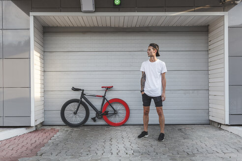 Young man with fixie bike at a roller shutter - VPIF00183