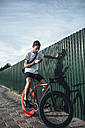 Young man using cell phone on fixie bike - VPIF00186