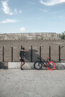 Young man standing at concrete wall next to fixie bike using cell phone - VPIF00192
