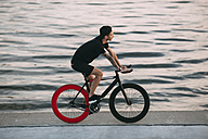 Young man riding fixie bike at the waterfront - VPIF00195