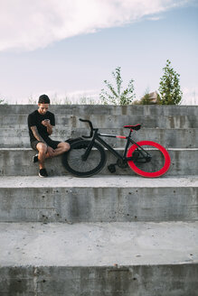 Young man sitting next to fixie bike using cell phone - VPIF00198