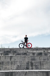 Young man standing with fixie bike on concrete steps - VPIF00201