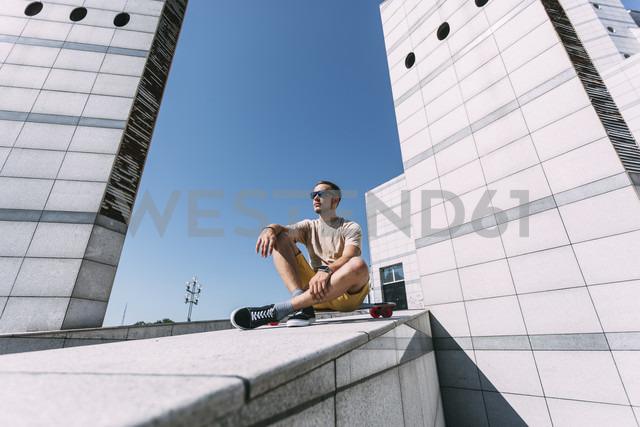 Young man with longboard surrounded by modern architecture - VPIF00207