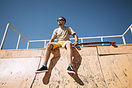Young man with earbuds and longboard sitting on top of halfpipe in skatepark - VPIF00213