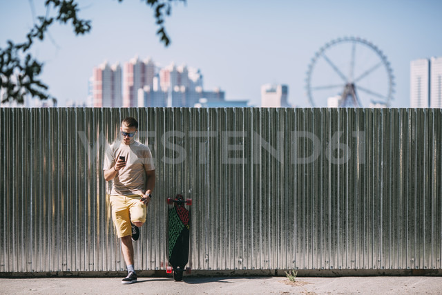 Young man with cell phone leaning against a wall next to longboard with city in background - VPIF00222