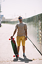 Portrait of confident young man with longboard - VPIF00225