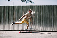 Young man riding skateboard along a wall - VPIF00228