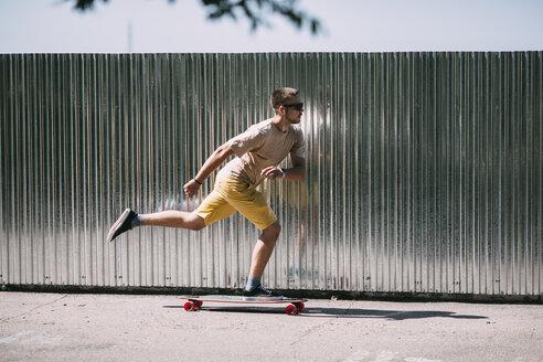 Young man riding skateboard along a wall - VPIF00228