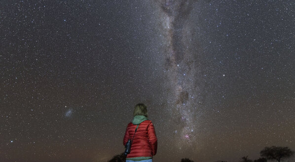 Namibia, Region Khomas, near Uhlenhorst, Astrophoto, Stargazing woman observing the Southern Cross embedded in the Milky Way band - THGF00005