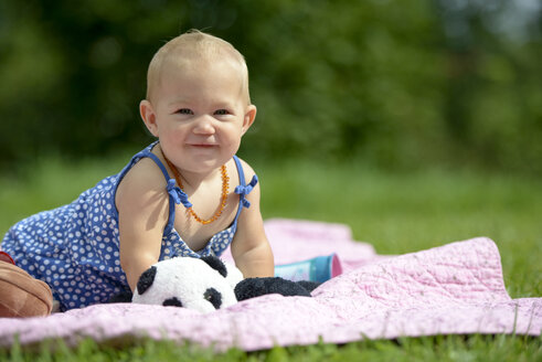 Portrait of smiling baby girl couching on blanket on a meadow - LBF01656