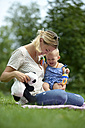 Mother playing with her baby girl in a park - LBF01659