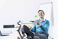 Smiling businessman juggling with balls in office - UUF11840