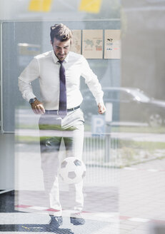 Businessman playing football in office - UUF11849