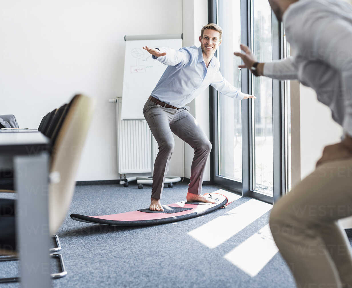 Two playful colleagues with surfboard in office - UUF11876 - Uwe Umstätter/Westend61