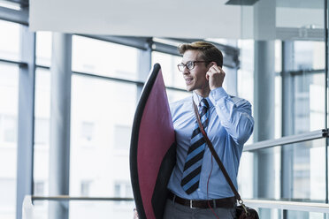 Businessman with earphones carrying surfboard in office - UUF11882