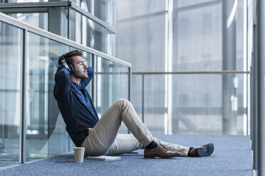 Businessman with headphones sitting on the floor relaxing - UUF11885
