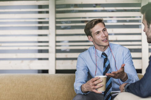 Businessman talking to colleague in office lounge - UUF11894