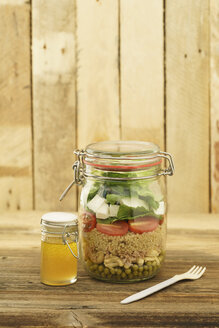 Preserving jar of mixed salad with peas, tuna, couscous, tomatoes, tuna, feta and jar of vinaigrette dressing - ECF01894