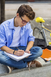 Young man with racing cycle sitting on bench writing on notepad - MGIF00142