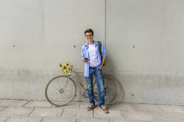 Smiling young man with racing cycle and cell phone in front of concrete wall - MGIF00151