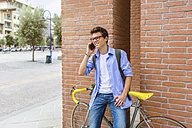 Portrait of smiling young man with racing cycle on the phone standing in front of brick wall - MGIF00157