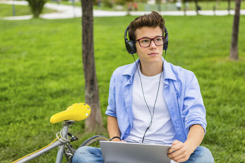 Portrait of serious young man with racing cycle sitting on a bench using laptop and headphones - MGIF00169