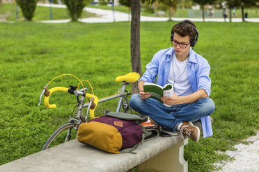 Young man with racing cycle and headphones sitting on a bench reading book - MGIF00172