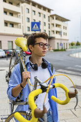 Portrait of young man carrying racing cycle on his shoulder - MGIF00175