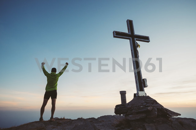 Italy, mountain running man cheering next to summit cross - SIPF01785 - Simona Pilolla/Westend61