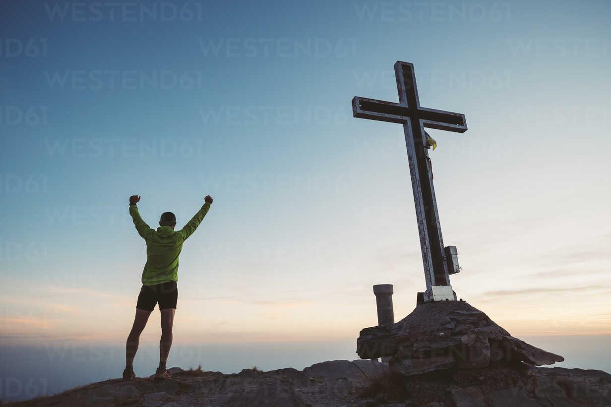 Italy, mountain running man cheering next to summit cross - SIPF01785 - Simona Pilolla/Westend61