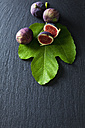 Sliced and whole figs and fig leaf on slate - CSF28299